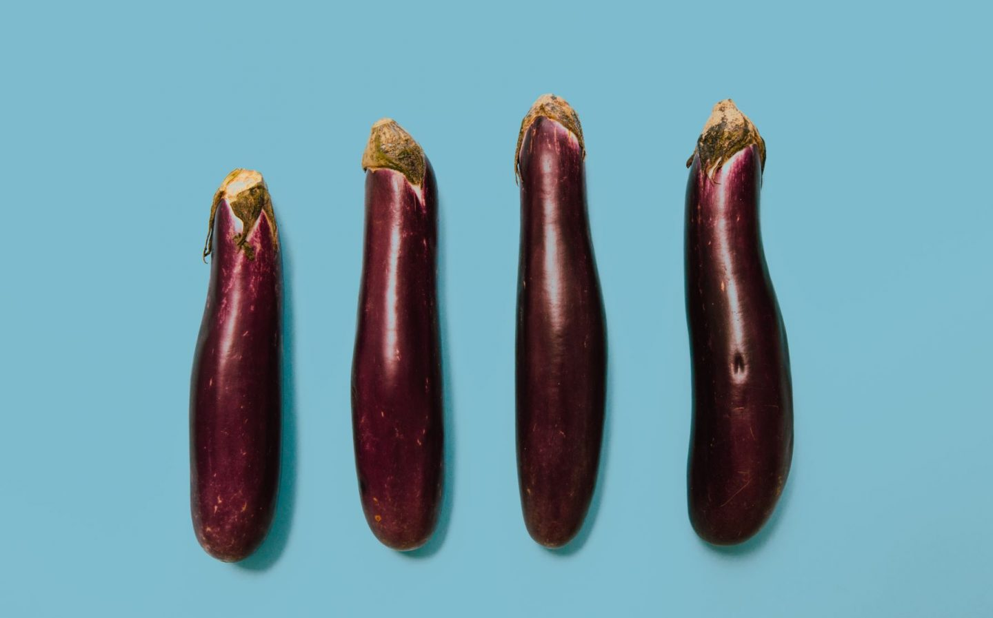 different sized aubergines in a line, as a metaphor for comparing lives!