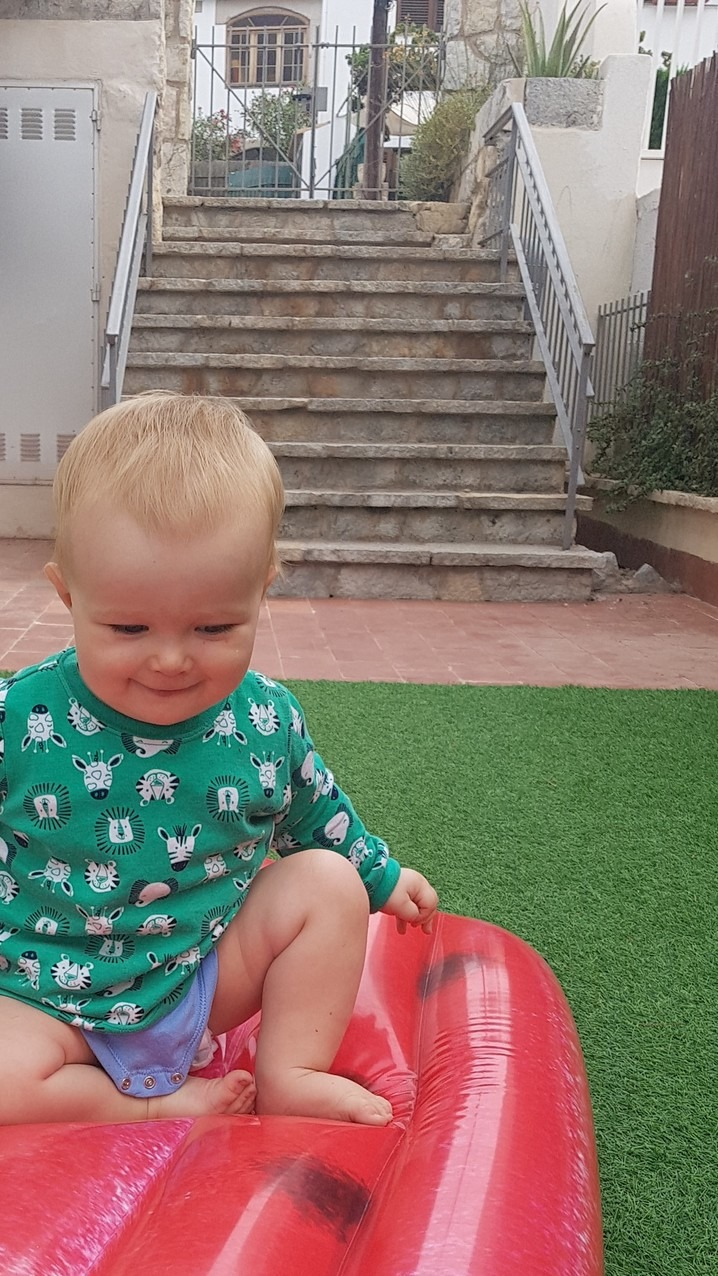 baby on an inflatable sunlounger in a garden