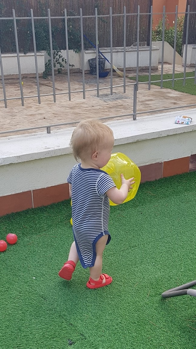 Baby carrying beach ball on holiday
