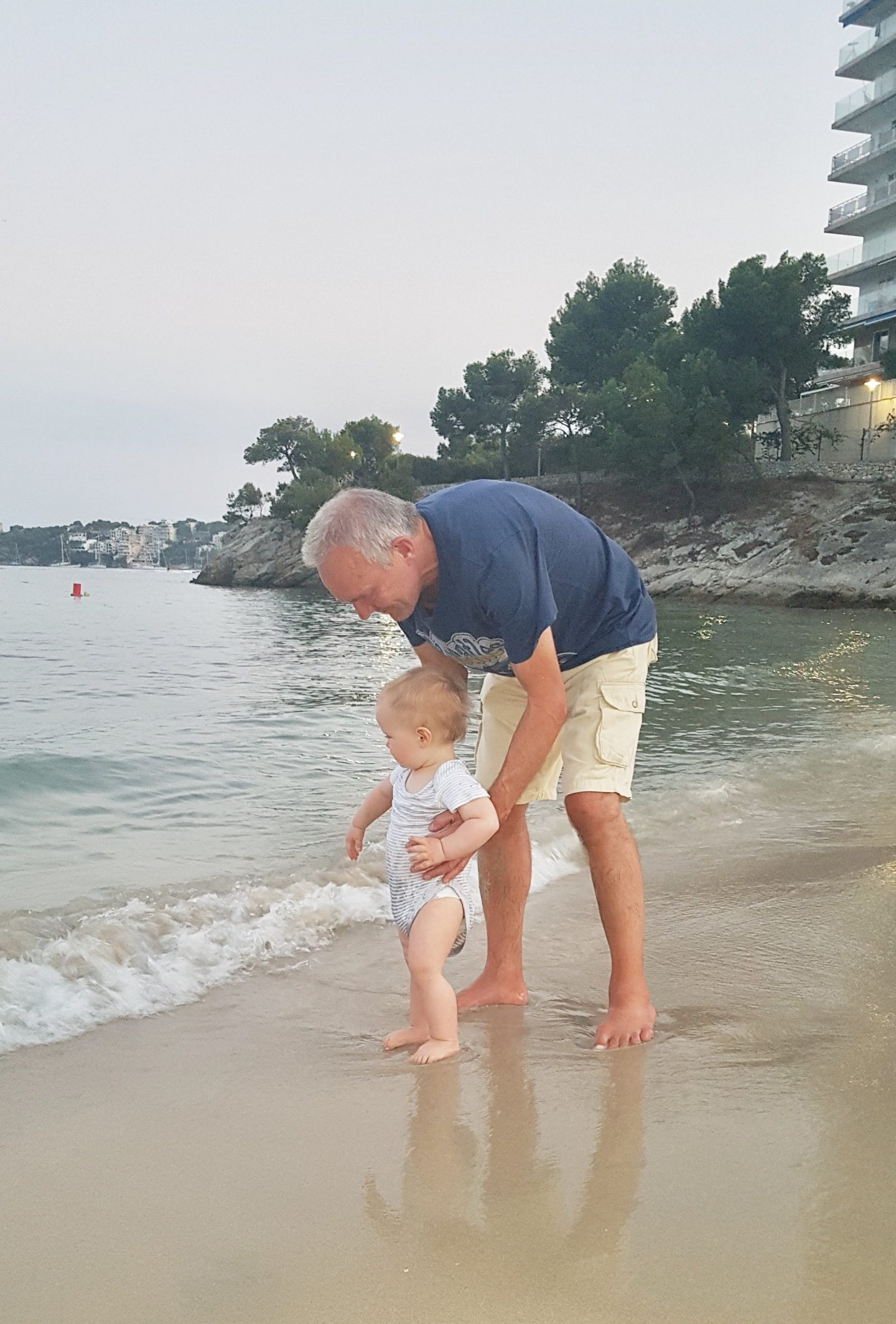 man and baby on beach at dusk