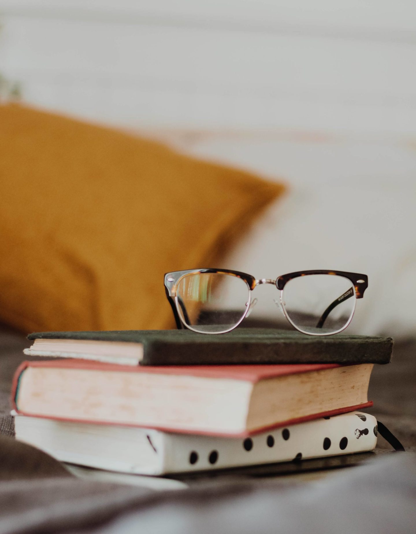 small pile of notebooks and books with a pair of glasses on top