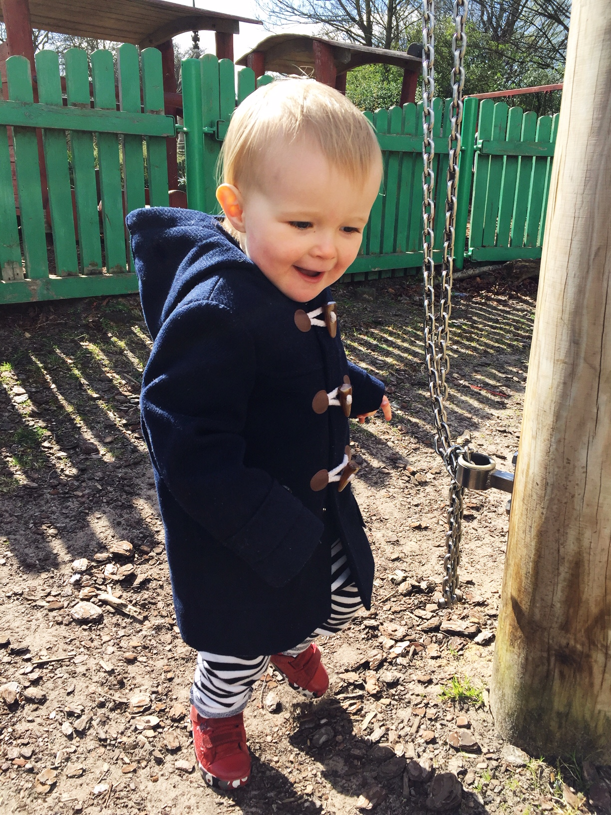 toddler boy in park wearing duffel coat