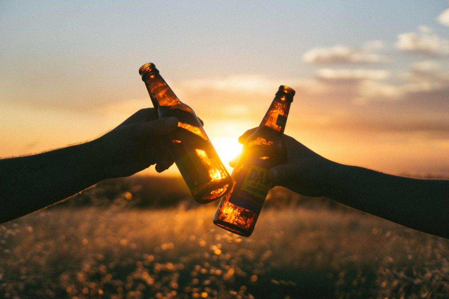 two beer bottles being clinked together